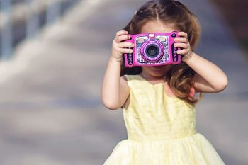 bambina con fotocamera giocattolo